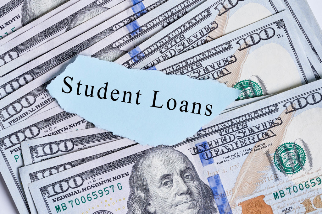 Text - Student loans on paper piece with a pile us dollar bills
