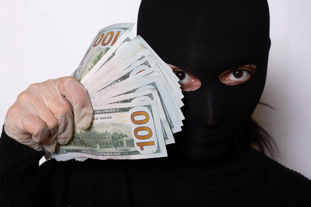 Portrait shot of a thief woman in black face mask holding a pile of stolen US dollars