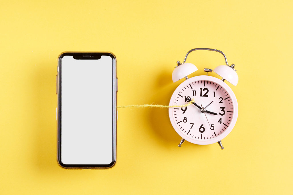 Smartphone with blank screen and classic alarm clock tied with a rope