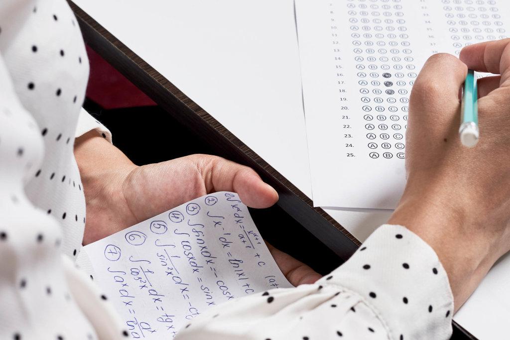 A student using math formula sheet to cheat on test