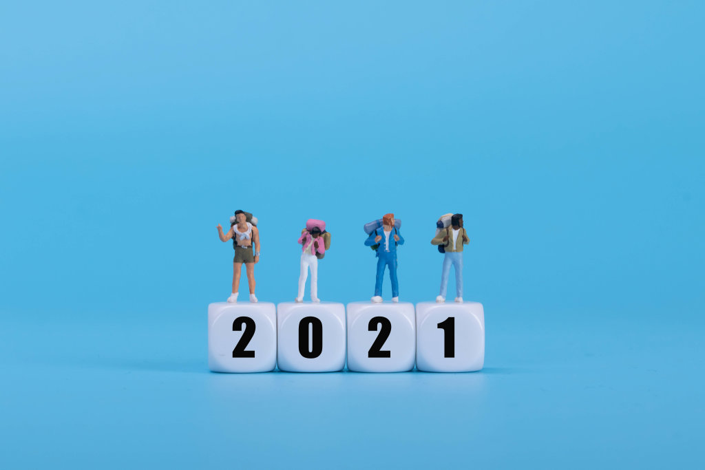 Travelers standing on white blocks with 2021 text on blue background