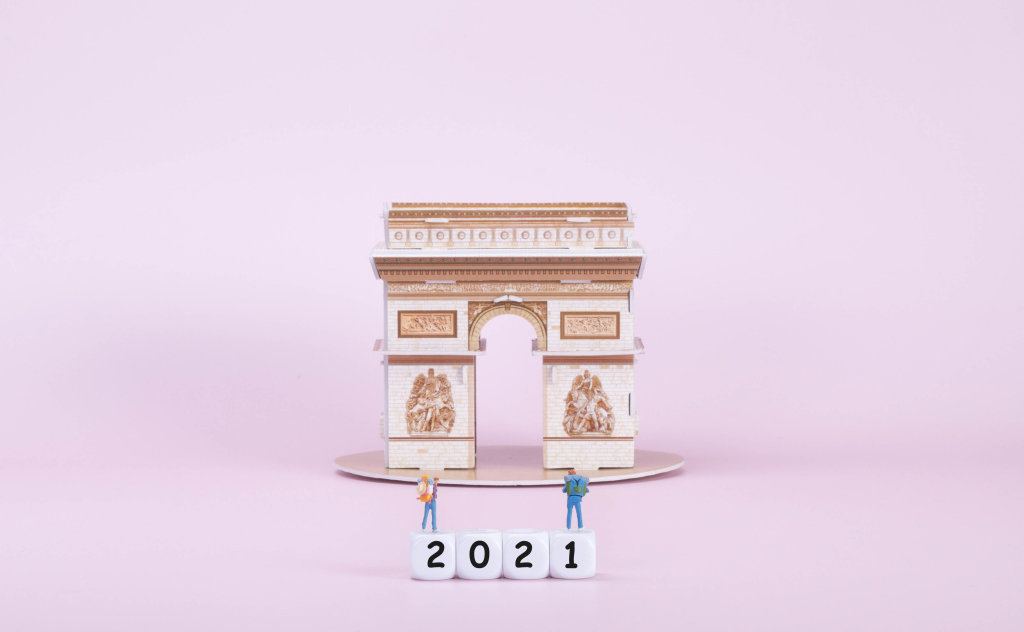 Two travelers standing on blocks with 2021 text in front of Arc de Triomphe