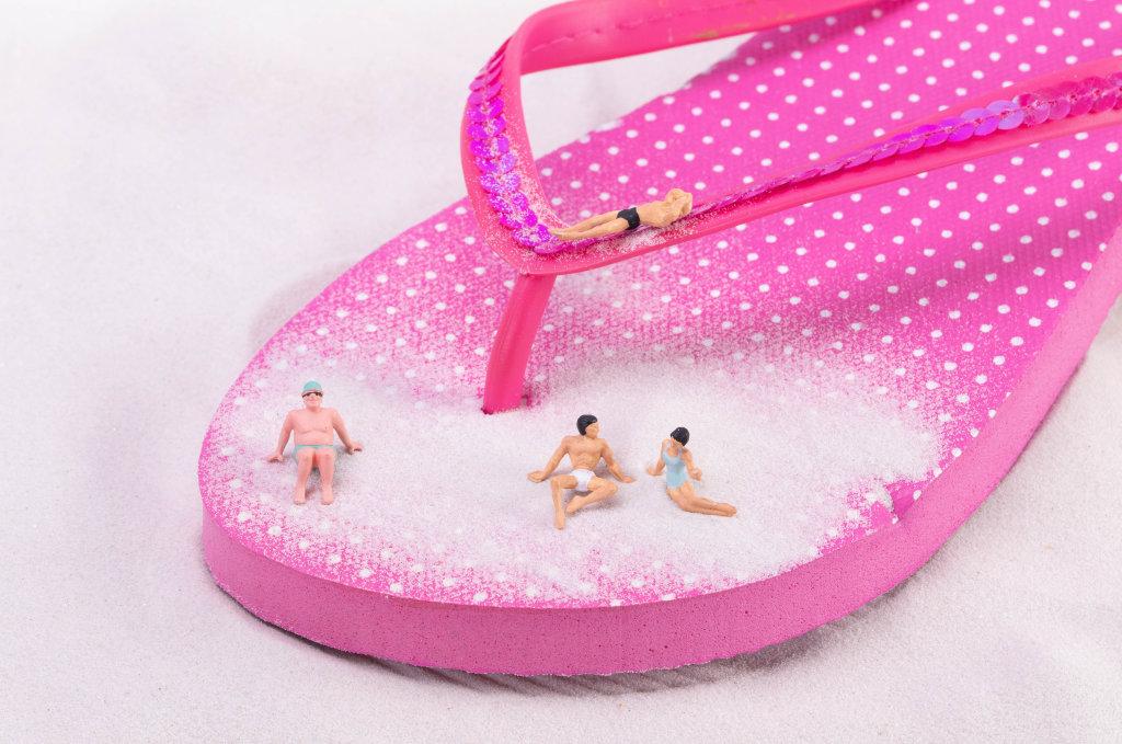 Miniature people relaxing on flip flops shoe