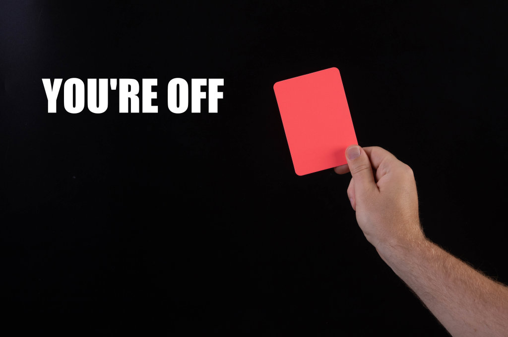 Hand holding red referee card with Youre off text on black background