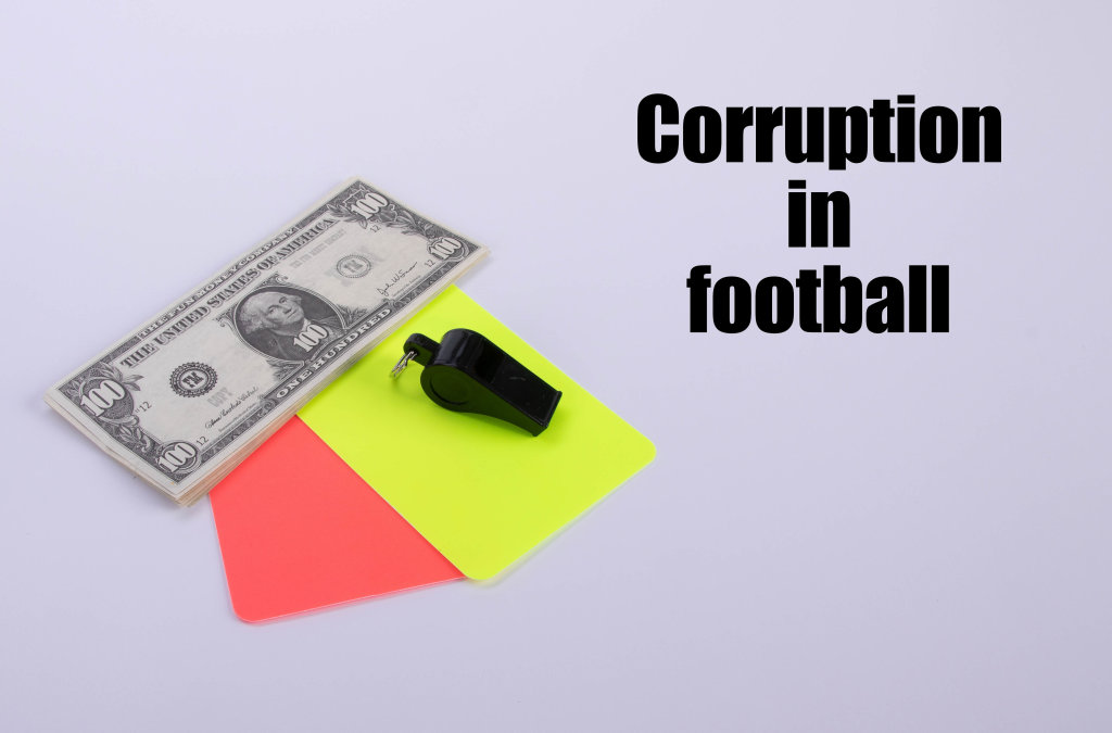 Red and yellow referee cards and a whistle with dollar banknotes and Corruption in football text
