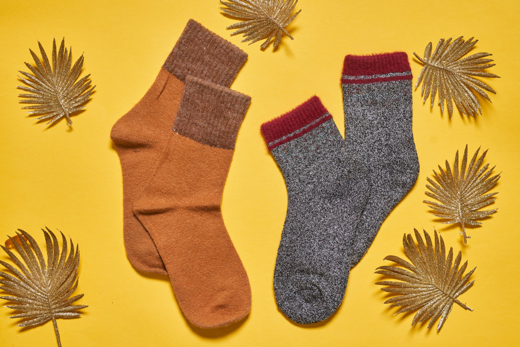 Two pairs of warm socks on yellow background with autumn leaves - for her and for him