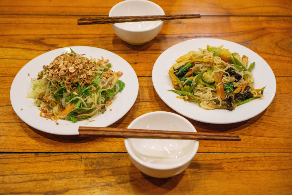 Food Photo of a Plate of Papaya Salad with Carrots, Mint, Fried Onions, Peanuts and Fishsauce next to a Plate of Fried Noodles with Vegetables on a Wooden Table with Bowls and Chopsticks