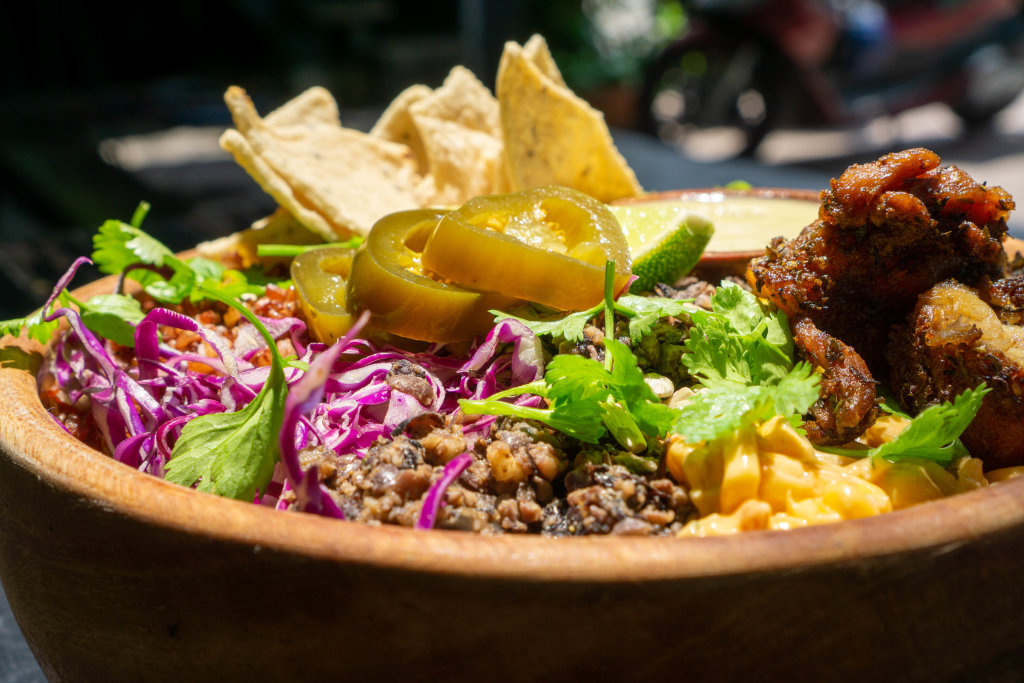 Close Up Food Photo of Healthy Bowl with Red Beans, Corn, Grilled Chicken, Cabbage, Jalapenos, Herbs, Tortilla Chips and Sauce in a Wooden Bowl