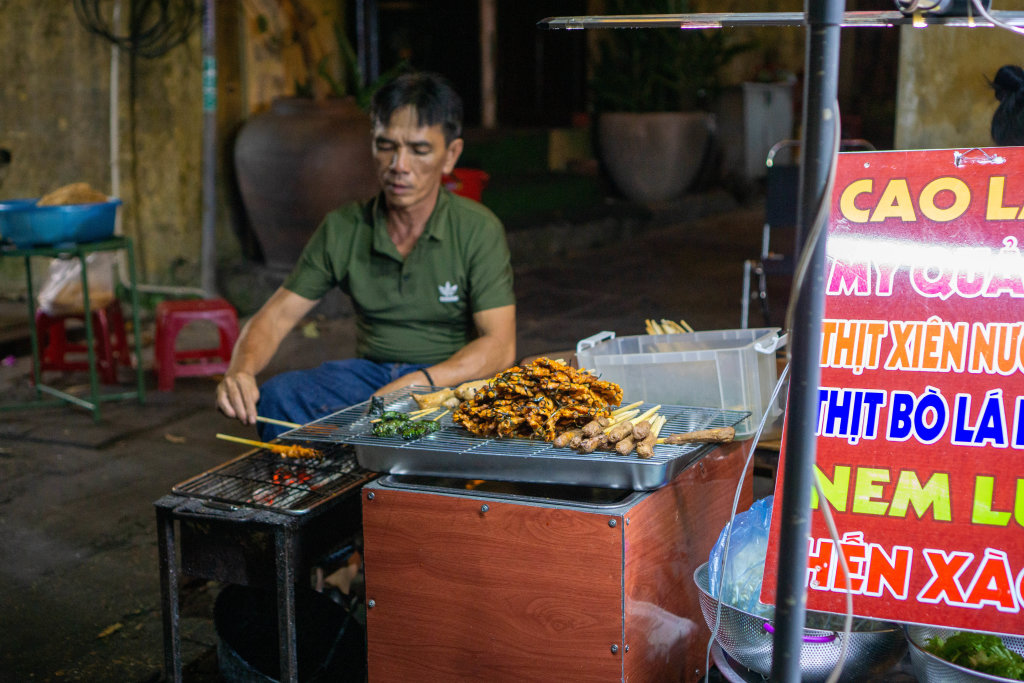 Vietnamese Man grilling Pork, Beef and Chicken Skewers on a Barbecue Grill at a Street Food Restaurant in Hoi An, Vietnam