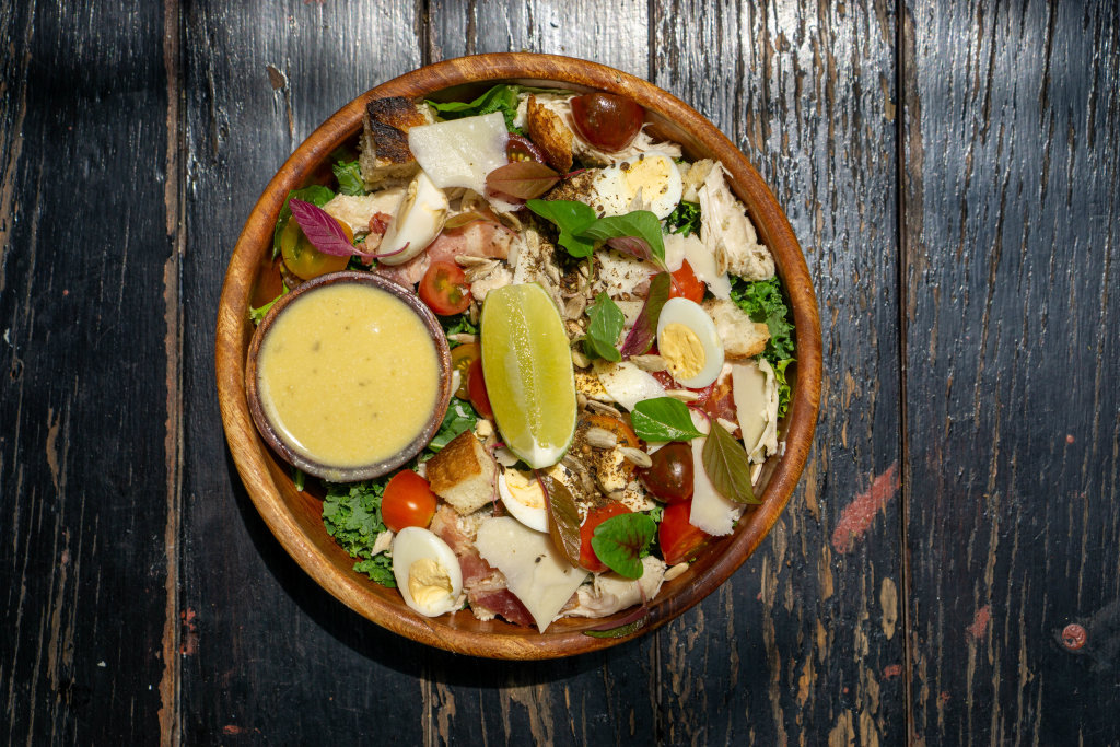 Top View Food Photo of Healthy Mixed Bowl with Boiled Chicken, Quail Eggs, Cherry Tomatoes, Parmesan Cheese, Basil, Lettuce, Lime and Honey Mustard Sauce on a Wooden Table