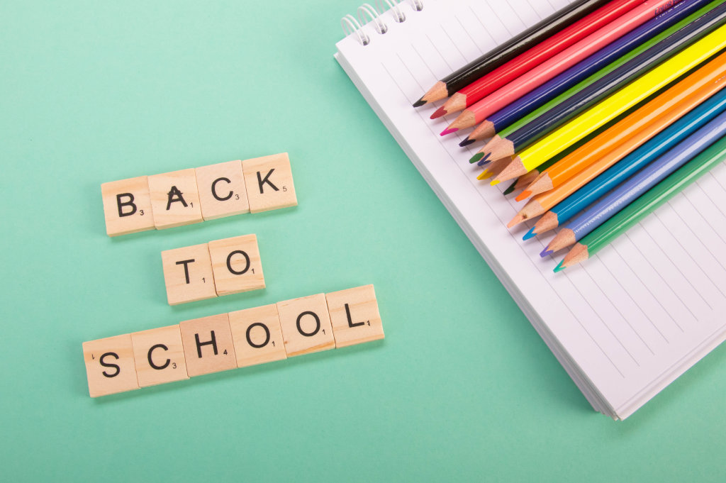 Colored pencils and wooden blocks with Back to School text on green background