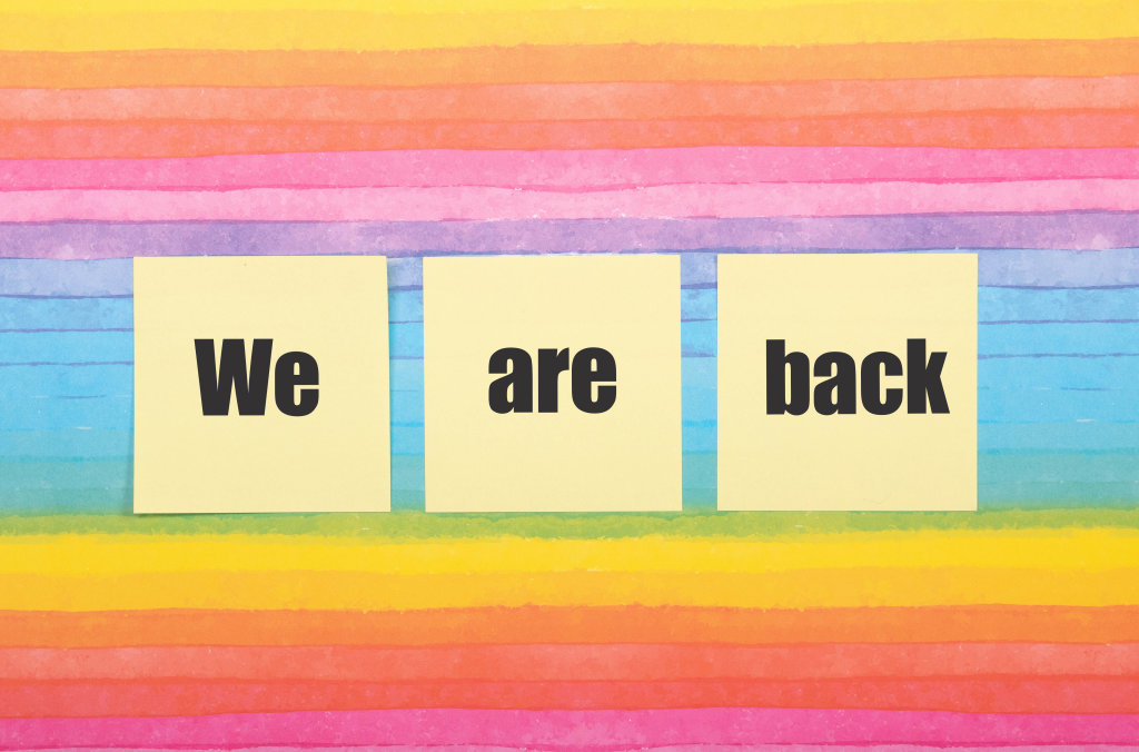 Sticky notes with We are back text on colorful background