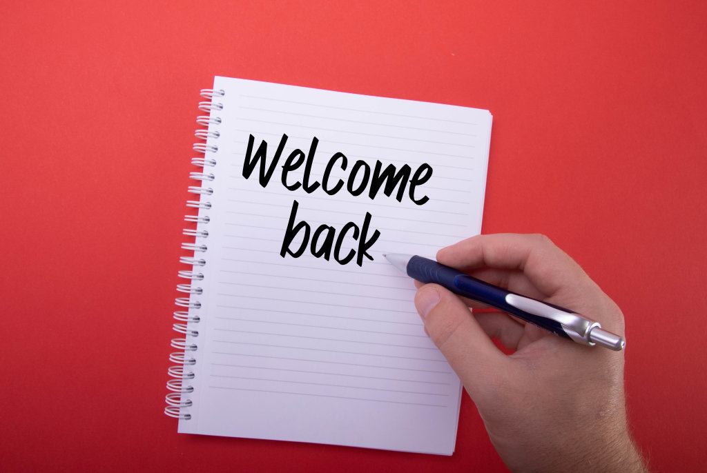 Hand writing Welcome back text in notebook on red background