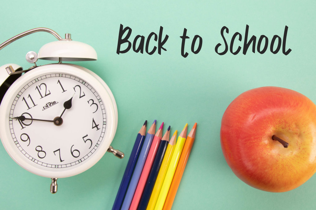 Alarm clock, colored pencils and apple with Back to School text