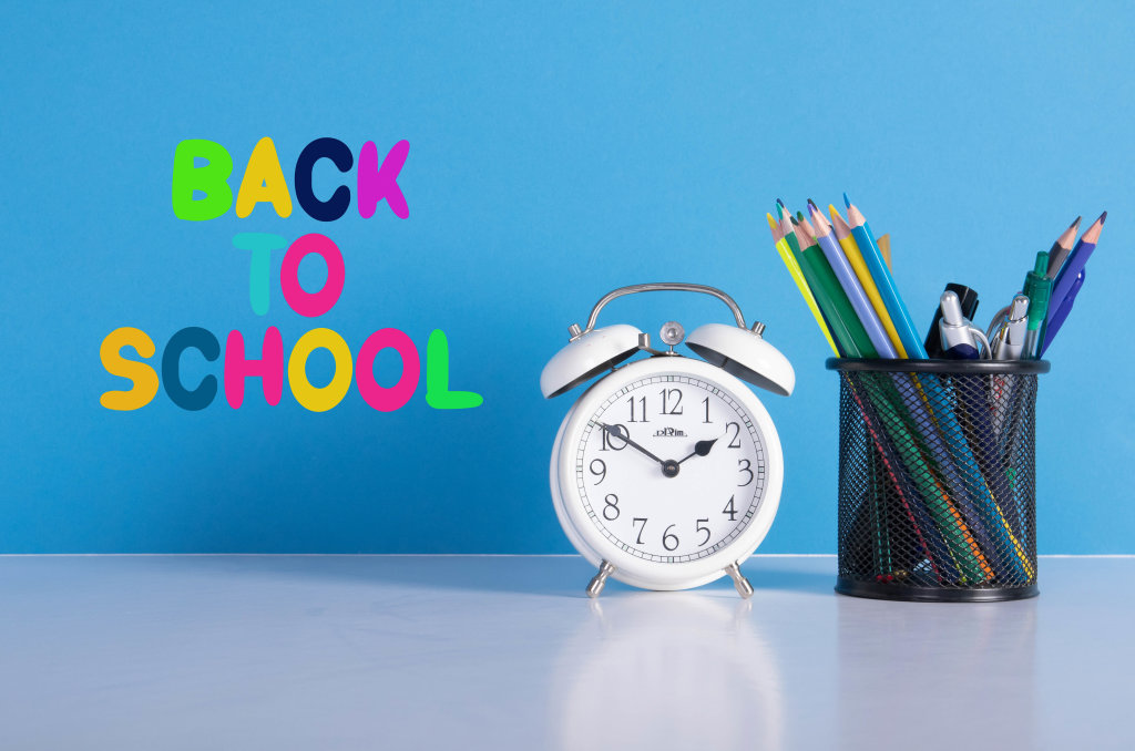 Alarm clock, colored pencils and back to School text on blue background