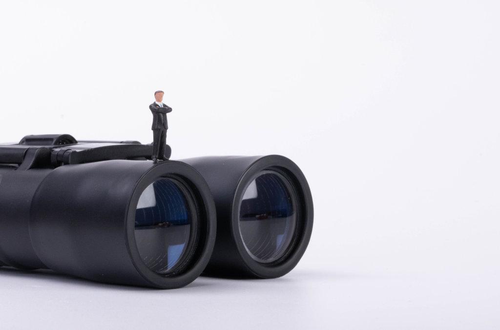 Businessman standing on a binoculars