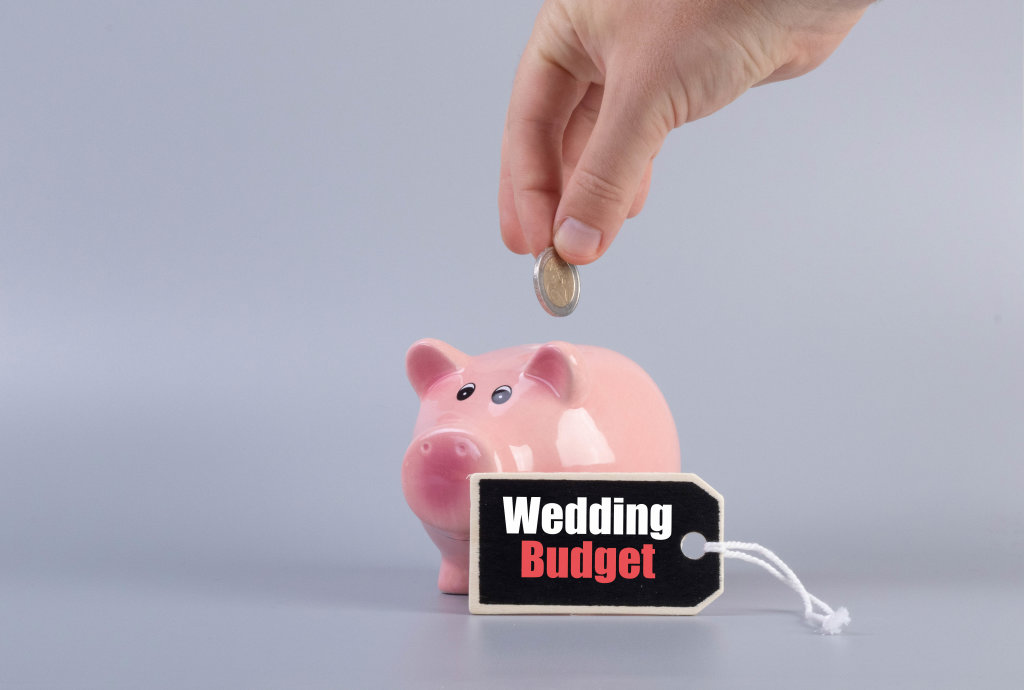 Hand putting coin in a piggybank and Wedding Budget text