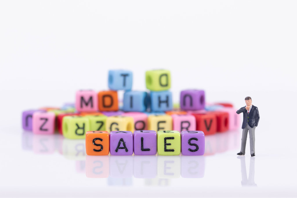 Businessman with colorful toy blocks with Sales text