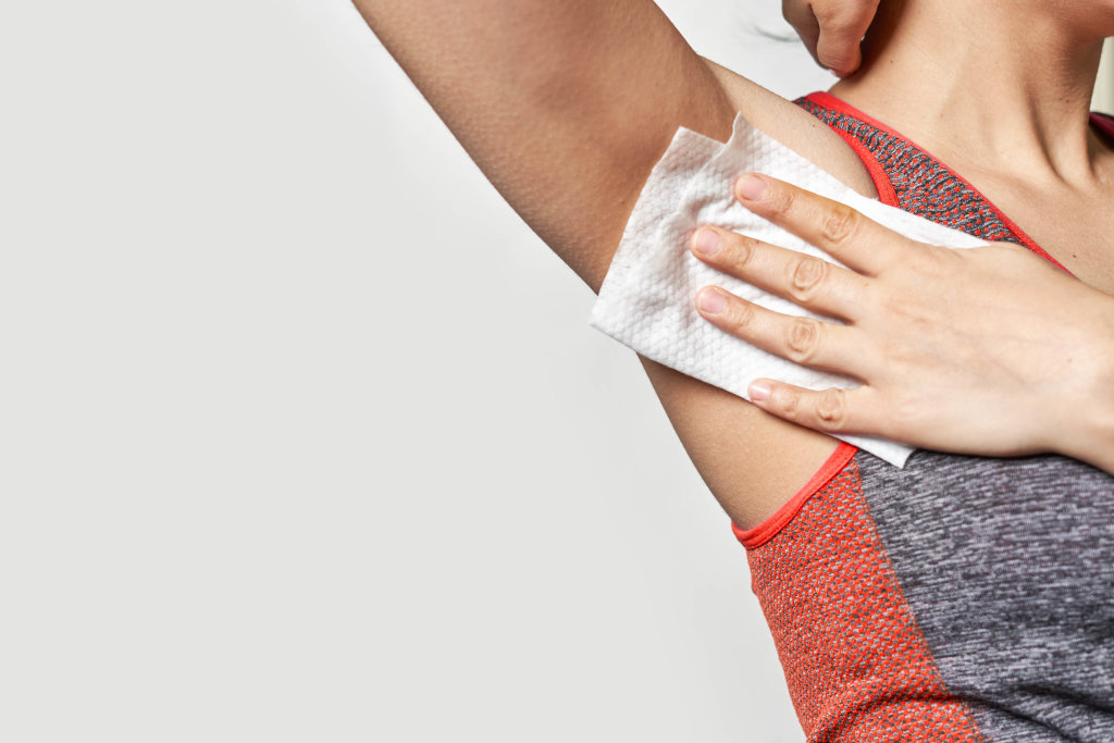 Woman cleans sweat from armpit with wet wipes after sport workout