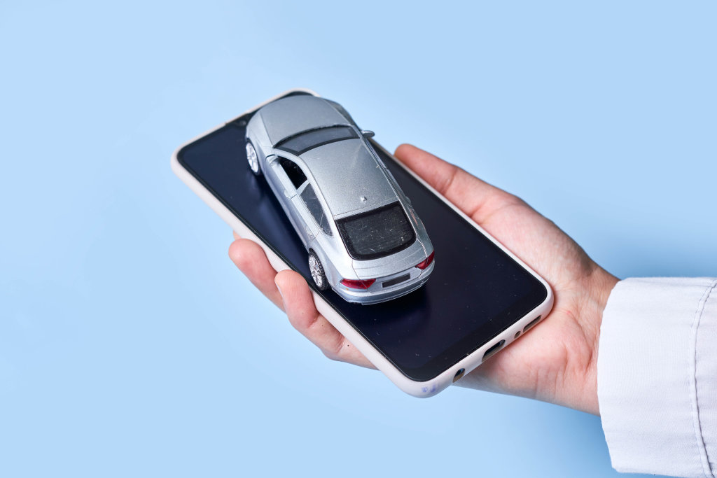 Woman hand holds smartphone and car toy. Concept of car sharing, calling taxi or delivery