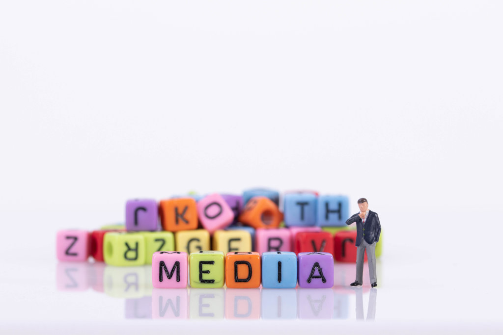 Businessman with colorful toy blocks with Media text