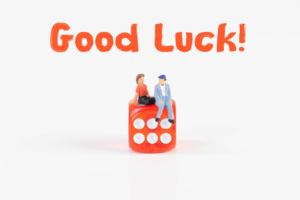 Couple sitting on a dice with Good Luck text