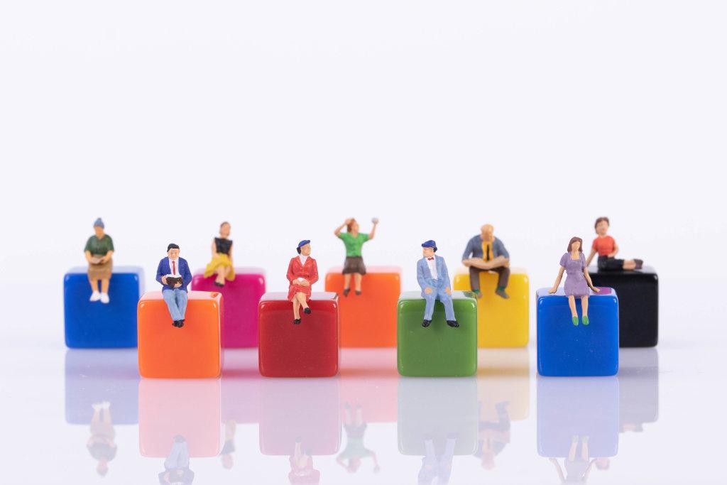 Miniature people sitting on colorful blocks