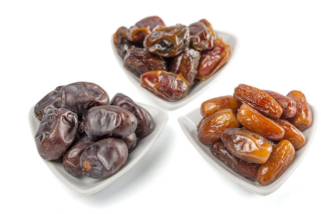 Three different kind of dried dates, fruits of date palm in white bowls