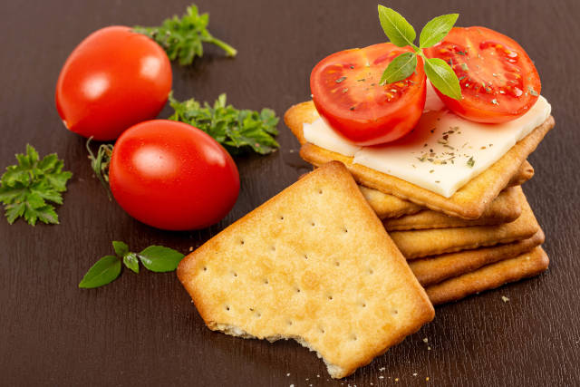 Delicious cracker snack with cheese and tomato