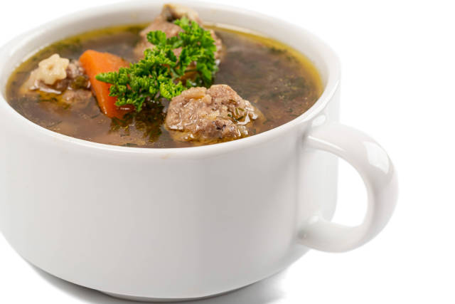Soup with meatballs in bowl on white background