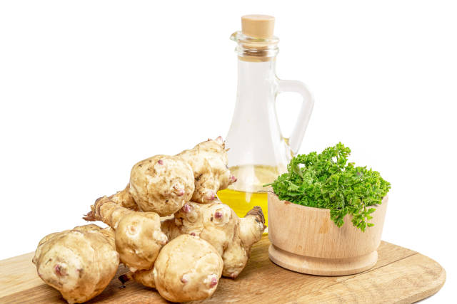 Jerusalem artichoke on a wooden cutting board with oil and parsley