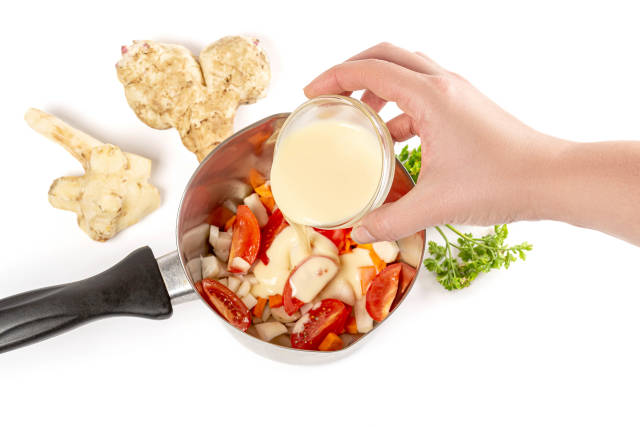 Sauce is poured into a saucepan with chopped vegetables, top view