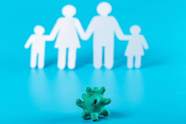 The virus is made from plasticine on a blue background with a silhouette of a family behind