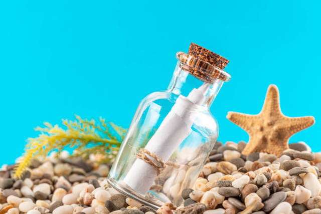 Message in a glass bottle on a blue background with stones and a starfish