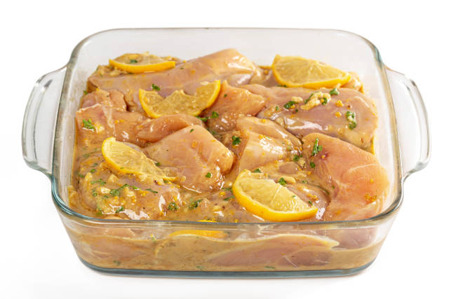 Marinated chicken pieces in a glass baking sheet, ready to bake