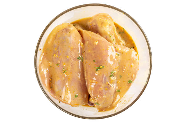 Chicken meat with marinade in a glass bowl, top view