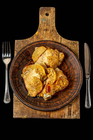 Baked chicken pieces with lemon on an old cutting board, dark background