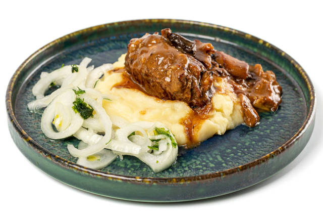 Mashed potatoes with meat roll, mushroom gravy and pickled onions