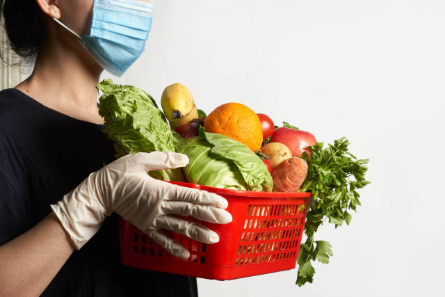 Delivery service worker in face mask and medical gloves brings ordered fresh vegetables
