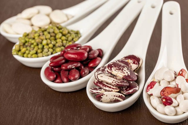 Assortment of beans in spoon, close up