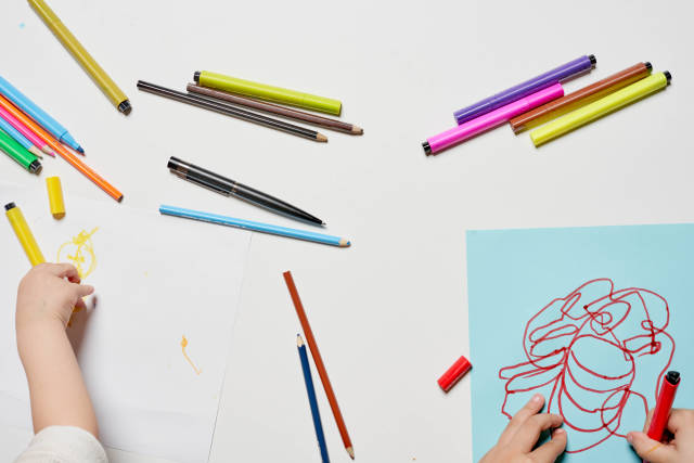 Two kids having fun drawing with colorful pens