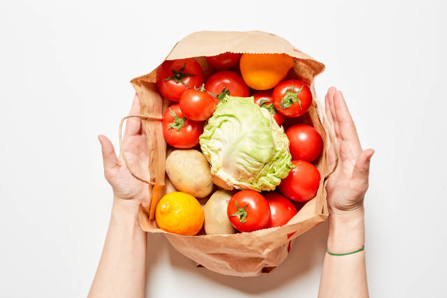 A person with healthy food in a paper bag - shopping food concept