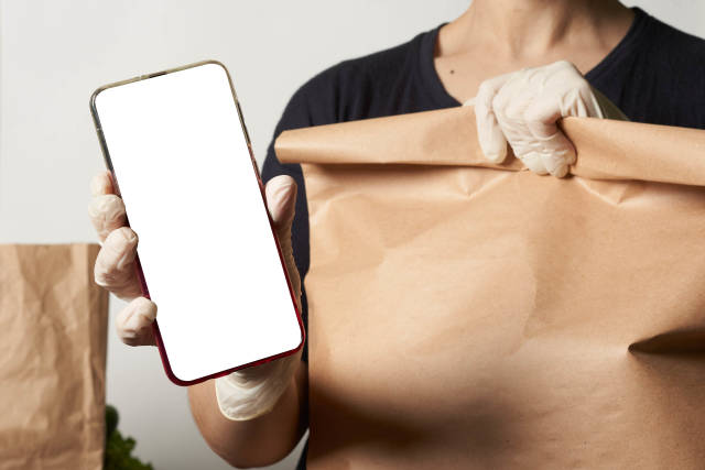 Delivery. A person in medical gloves holding a paper shopping bag and smartphone with a blank screen