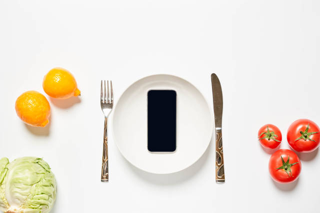 Empty plate with mobile phone and fresh tomatoes, lemons and cabbage