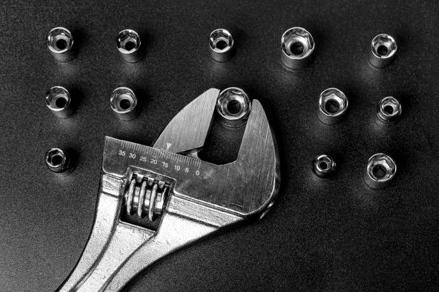 Adjustable wrench and screwdriver heads on black background