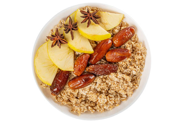 Top view, oatmeal with dates and apple on a white background