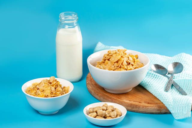Cornflakes with milk for breakfast, blue background