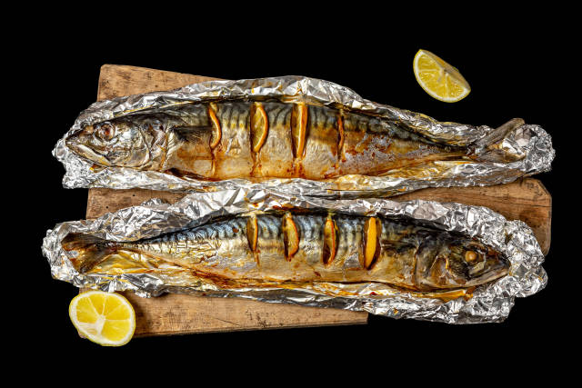 Two baked mackerel with lemon slices in foil, top view