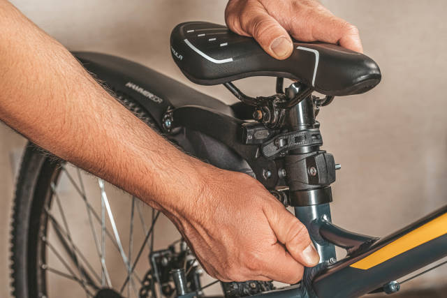 Male hands fixing the bike seat