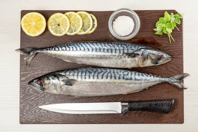 Raw mackerel on brown cutting board